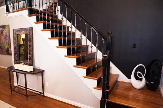 Change out the spindles, paint the handrail and newell posts and give them an artistic finial. Paint the wall and risers black and Voila! Amazing Transformation!